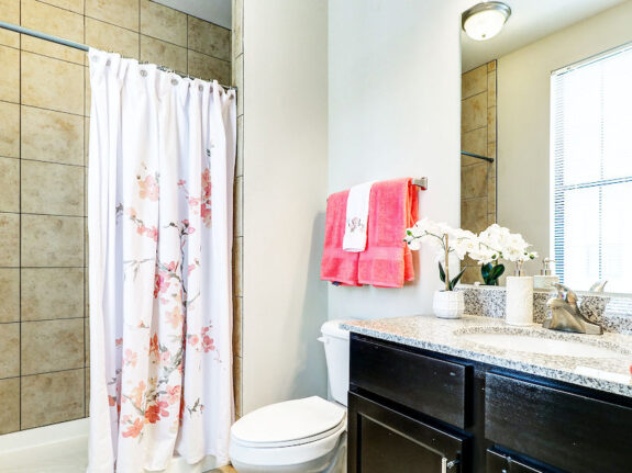 Townhome bathroom with pink towels, black drawers and flower patter on shower curtain.