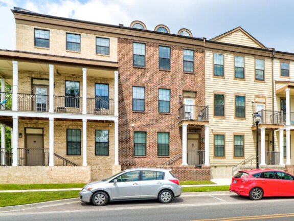 The Betty townhomes with yellow and brown tones balconies and cars parked on the street
