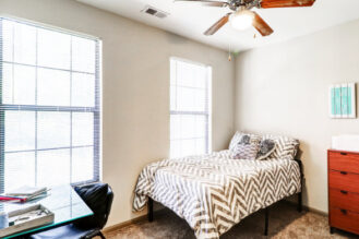 Two window student bedroom with drawer, ceiling fan and desk on the corner.